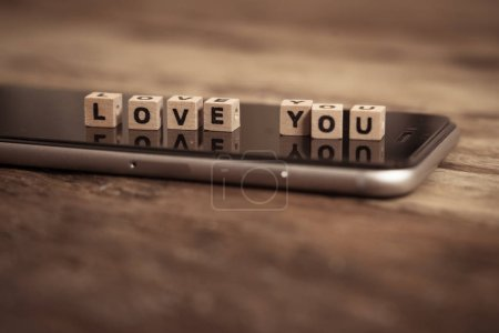 Photo for Valentine day internet messaging concept, online connection, online dating and advertising concept. Conceptual image of Mobile phone on rustic wood with with text Love you in wood blocks, top view. - Royalty Free Image
