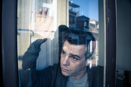 Photo for Close up portrait of young sad unhappy caucasian man looking worried, desperate and suicidal through the window at home. feeling worthless and in pain. In People, Depression and crisis concept. - Royalty Free Image