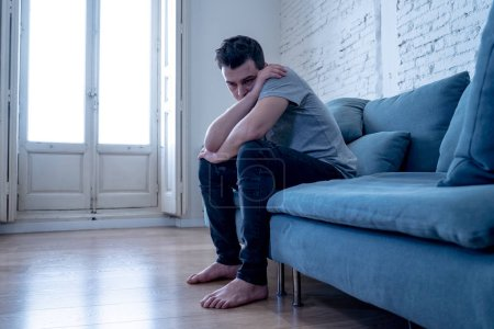 Photo pour Portrait de jeune homme abattage déprimée et désespérée pleurer seul dans le canapé accueil souffrant le malheur et la douleur émotionnelle. Dans gens Broken heart, intimidation dépression mentale problèmes de santé et concept. - image libre de droit