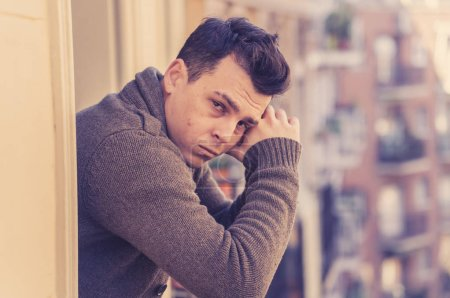 Photo for Sad unhappy depressed young man crying and suicidal feeling desperate, isolated and worthless staring down the street on home balcony In People Depression and Mental Health concept. Urban background. - Royalty Free Image
