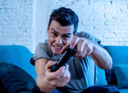 Foto de Retrato de joven estudiante hombre pasar el tiempo jugando video juegos joystick control remoto inalámbrico con cara feliz intenso freak que se divierten en la adicción masculina juego para consola play station y video. - Imagen libre de derechos