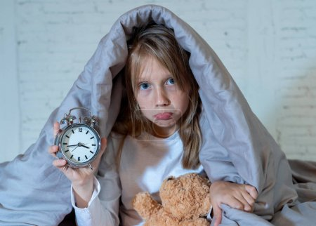 Photo for Cute sleepless little girl sitting on bed looking sad and tired having sleeping troubles staying asleep at night or waking too early in the morning in Insomnia Anxiety Sleep Disorders in children. - Royalty Free Image