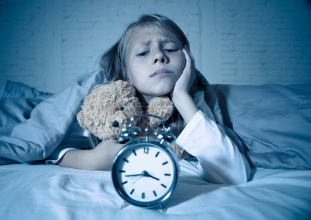 Photo for Cute sleepless little girl lying in bed showing alarm clock looking tired having sleeping troubles staying asleep at night or waking too early in Children Insomnia Anxiety and Sleep Disorders. - Royalty Free Image
