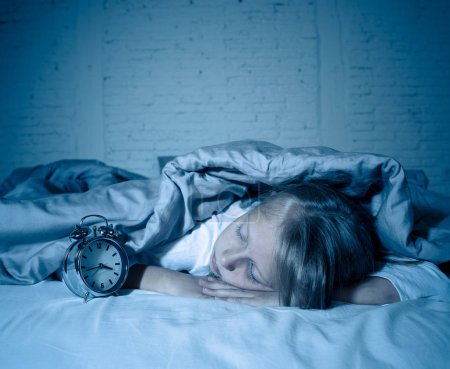 Photo for Cute sleepless little girl lying in bed looking sad and tired having sleeping troubles staying asleep at night or waking too early in the morning in Insomnia Anxiety Sleep Disorders in children. - Royalty Free Image