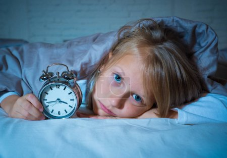 Photo for Cute sleepless little girl in bed awake in the middle of the night looking tired having troubles staying asleep at night or waking up too early in Insomnia Anxiety Sleeping Disorders in children. - Royalty Free Image