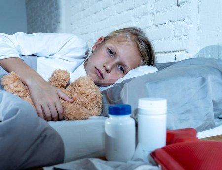 Photo pour Douce fille mignonne malade malade couché dans son lit avec médicaments thermomètre à eau chaude souffrant du froid et hiver grippe Virus éternuements exécutant nez et calmant pour les symptômes de la maladie en soins de santé infantile. - image libre de droit