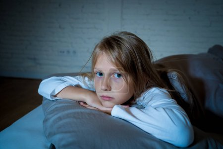 Photo for Cute little caucasian girl lying in bed covering her head with blanket feeling exhausted and sleepless suffering from insomnia Depression Stress in Children Emotional and Sleeping Disorders concept. - Royalty Free Image