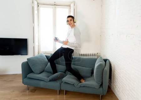 Photo for Portrait of young happy teenager male listening to music in headphones singing and dancing on couch sofa having fun at home. In positive emotions and happiness,Leisure Music and technology concept. - Royalty Free Image