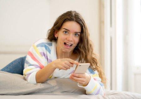 Photo pour Femme heureux jeune adolescent attrayant sur téléphone intelligent vérifiant les disciples et le chat en ligne en utilisant une application mobile à la maison en communication, internet, médias sociaux et nouveau concept de technologie. - image libre de droit
