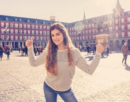 Foto de Mujer hermosa joven turista feliz y emocionada en Plaza España busca alcalde Madrid alegre diversión y haciendo pulgar arriba signo en día soleado. En turismo, viajar por Europa y año sabático de estudiante. - Imagen libre de derechos