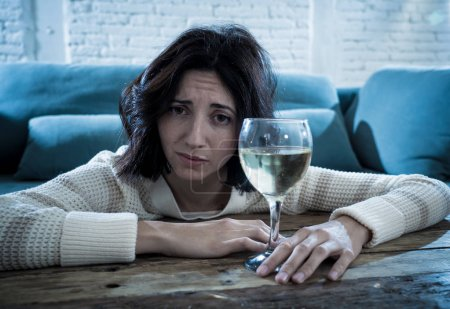 Photo for Stressed and hopeless young woman drinking a glass of wine alone at home. Feeling depressed, frustrated and weak, trying to feel better drinking. Unhealthy behavior, depression and alcoholism concept. - Royalty Free Image
