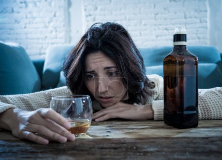 Photo for Drunk alcoholic depressed woman drinking scotch whiskey spirits alone at home. Feeling hopeless, week and lonely. In People lifestyle, Depression, alcohol addiction, alcoholism and drug abuse concept. - Royalty Free Image