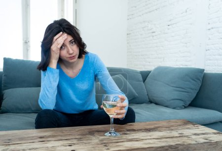 Photo for Portrait of depressed woman drinking glass of wine alone at home. Feeling distress, hopeless and frustrated, trying to feel better drinking. Unhealthy behavior, depression and alcohol concept. - Royalty Free Image