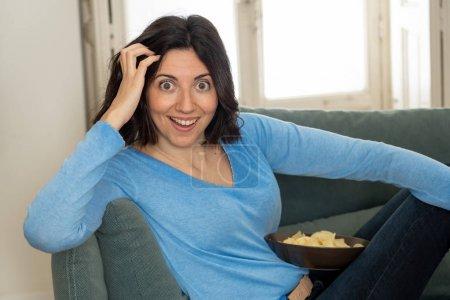 Photo pour Femme heureuse sur le sofa avec la télécommande de tv prête à regarder le film préféré de tv Show. Vous cherchez enthousiaste, faire des gestes d'approbation et de manger des frites. Dans les personnes, la technologie et le concept de loisirs. - image libre de droit