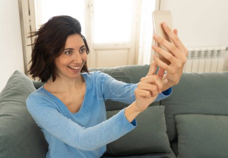 Photo for Attractive woman taking a funny selfie on mobile phone smiling for her followers in social media at home. Blogger woman on smartphone recording video. In leisure internet and social network concept. - Royalty Free Image