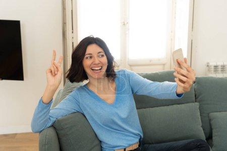 Photo pour Femme attrayante prenant un selfie drôle sur téléphone mobile souriant pour ses disciples dans les médias sociaux à la maison. Blogueuse femme sur smartphone enregistrement vidéo. Internet de loisirs et concept de réseau social . - image libre de droit