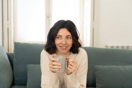 Photo pour Verticale de style de vie de jeune femme assez détendue buvant le café chaud ou le chocolat se sentant heureux et confortable à la maison souriant heureux sur le divan. Dans les loisirs, la vie paisible, le concept de style de vie de bonheur. - image libre de droit