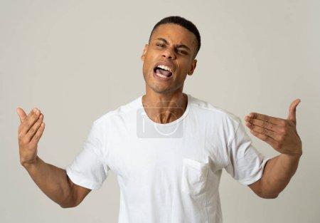 Photo pour Fermez-vous vers le haut du portrait d'un jeune homme américain africain attrayant avec le visage fâché semblant furieux et fou ayant une dispute ou une lutte. Chez les gens, les expressions faciales humaines et les émotions négatives. - image libre de droit