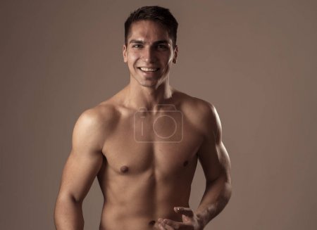 Photo for Strong sexy handsome Athletic man laughing and feeling good after workout. Studio shot of Mixed race latin fitness model posing for sports, beauty or fashion advertisement. In happy healthy lifestyle. - Royalty Free Image