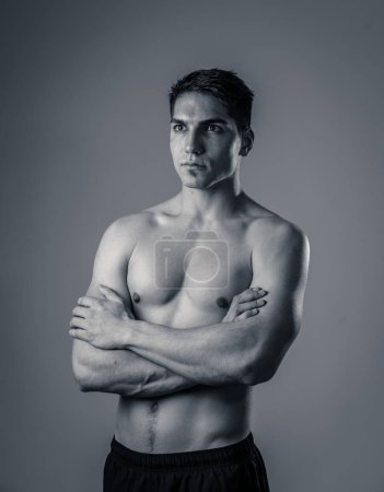 Photo for Strong handsome Athletic young man isolated on neutral background. Mixed race latin muscly model posing for fitness marketing advertising. In exercise, healthy lifestyle, workout and body care. - Royalty Free Image