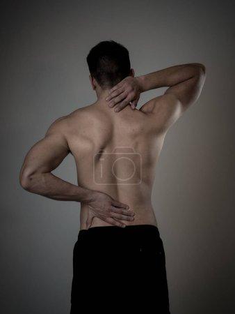 Foto de Joven hombre musculoso fitness tocando y agarrando su cuello y la parte baja de la espalda sufriendo dolor cervical aislado en el fondo neutro. En el deporte y las lesiones en el entrenamiento, problemas de postura incorrectos y cuidado del cuerpo. - Imagen libre de derechos