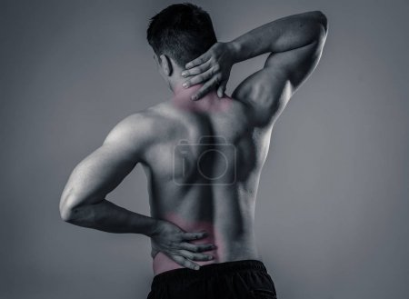 Photo for Young muscular fitness man touching and grabbing his neck and lower back suffering cervical pain isolated on neutral background. In sport and workout injury, Incorrect posture problems and body care. - Royalty Free Image