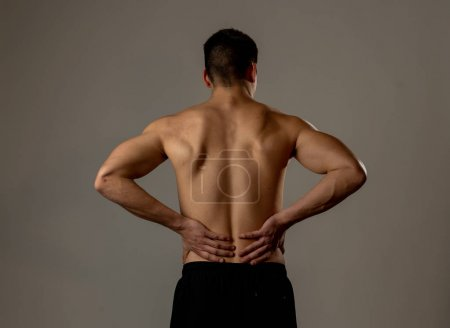 Photo for Young muscular fitness man touching and grabbing his lower back suffering strong pain after workout. Isolated on neutral background. In sport injury Incorrect posture problems and body health care. - Royalty Free Image