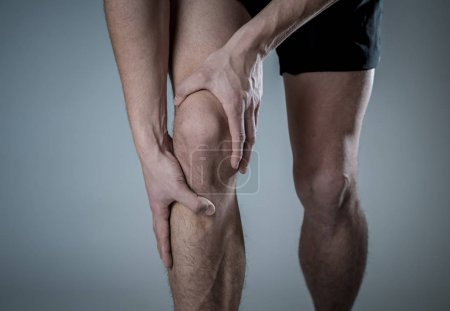 Foto de Joven hombre de ajuste sosteniendo la rodilla con las manos en el dolor después de sufrir lesión muscular roto dolor en la pierna ósea o calambres durante el entrenamiento de carrera. En el dolor corporal y el entrenamiento deportivo lesiones y cuidado de la salud corporal. - Imagen libre de derechos