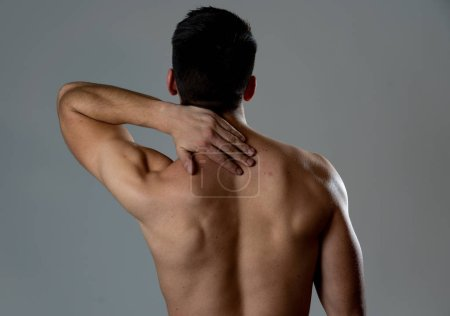 Photo for Young muscular fit man touching and grabbing neck and upper back suffering cervical pain after workout. Isolated on neutral background. In sport injury Incorrect posture problems and body health care. - Royalty Free Image