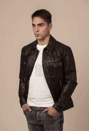 Photo for Portrait of young attractive fashion hipster man model in his 20s in black leather jacket posing against neutral background looking sexy and masculine. In People, multiracial and Beauty concept. - Royalty Free Image
