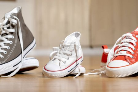 Photo for Conceptual image of gumshoes sneakers shoes of father mother and son daughter family on wood floor in different sizes in Sweet home togetherness Happy Family Parenting and expecting a baby concept. - Royalty Free Image