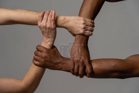 Photo pour Races unies contre la discrimination et le racisme. Mains noires afro-américaines et caucasiennes tenant ensemble dans l'unité du monde et l'amour et la compréhension raciales. Concept de tolérance et de coopération. - image libre de droit
