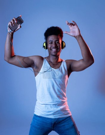 Photo for Strong african american young dancer man listening to music online dancing and singing with headphones. Artistic portrait with disco dance floor neon light in Internet Music and technology concept. - Royalty Free Image