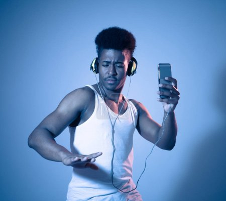 Photo for Strong african american young man listening to music online in smartphone app dancing and singing with headphones. Close up portrait with disco dance floor neon light in Music and technology concept. - Royalty Free Image