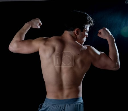 Photo for Strong Athletic Man model showing six pack abs, back and torso. Bodybuilder sexy muscular guy with athlete muscly body posing against black background In body care fitness, bodybuilder and workout. - Royalty Free Image