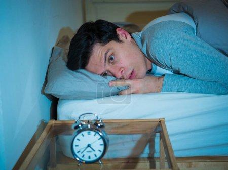 Photo pour Jeune homme caucasien insomniaque et désespéré réveillé la nuit incapable de dormir, se sentant frustré et inquiet en regardant l'horloge souffrant d'insomnie dans le stress et les troubles du sommeil concept . - image libre de droit