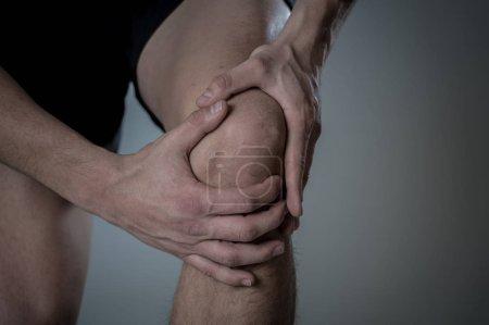 Photo pour Jeune homme en forme tenant le genou avec les mains dans la douleur après avoir subi une blessure musculaire fracture des jambes douleurs osseuses entorse ou crampe pendant l'entraînement de course. Douleur corporelle et entraînement sportif blessures et soins de santé corporels . - image libre de droit