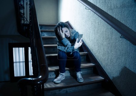 Photo for Sad depressed young teenager girl victim of cyberbullying by mobile smart phone siting on stairs feeling lonely, unhappy, hopeless and abused. Bullied by text message on social media app. Dark light - Royalty Free Image