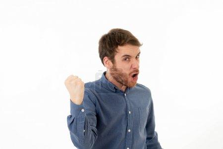 Photo pour Portrait de jeune homme heureux et excité remportant la loterie célébrant le but ou ayant un grand succès avec poing vers le haut acclamant. Dans les gens succès et expression faciale et émotions humaines positives . - image libre de droit