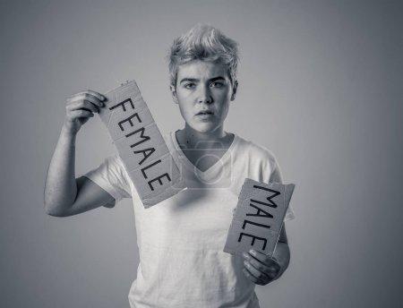 Photo pour Adolescent transgenre beau déchirant le mot Femme en HOMME dans l'identité de genre, l'égalité et les droits de l'homme. Briser le silence sur son identité de genre transgenre concept de fierté et de liberté . - image libre de droit