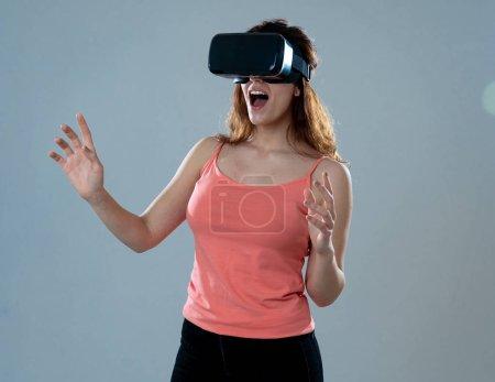 Photo pour Femme séduisante incroyable utilisant des lunettes de casque VR toucher et interagir avec le monde de la réalité virtuelle. Je me sens excité d'explorer et de m'amuser dans la simulation 360 VR. Innovation et nouvelles technologies . - image libre de droit