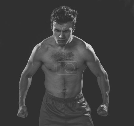 Photo for Portrait of strong muscular sports man with an intense furious look. Expressive sexy shirtless angry man looking powerful on black background in Workout, training and fitness concept. - Royalty Free Image