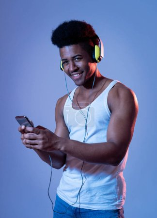 Photo for Strong african american young man listening to music in smartphone app looking for best song online with headphones singing and dancing. Portrait with disco dance floor light in Music and technology. - Royalty Free Image