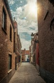 Alley with brick walls and sunshine at City Center of Bruges