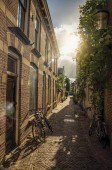 Alleyway with brick houses and bikes on sunset in Weesp