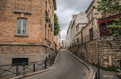 Facade of old building in an alley and cloudy sky in Paris