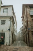 Old houses and deserted alley in the morning mist