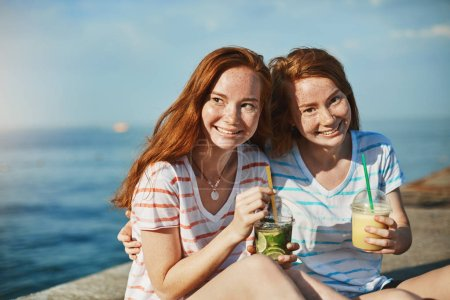 Photo for Sharing best moments. Two gorgeous girls with red hair and freckles sitting near seashore and drinking cocktails, hugging and enjoying spending time together, feeling relaxed and happy. - Royalty Free Image