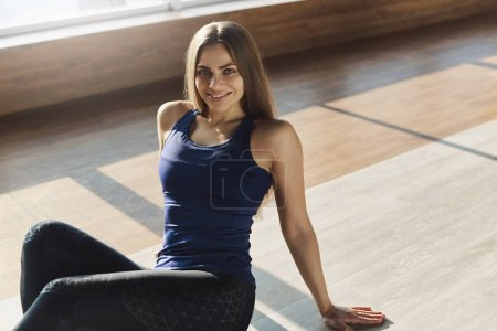 Photo for Young healthy sporty woman enjoying working-out lying on floor smiling satisfied with good productive training session with coach in yoga studio wearing activewear to perform fitness exercises. - Royalty Free Image