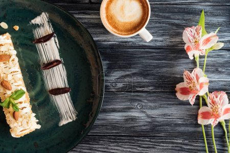 top view of sweet tasty dessert on plate, cup of cappuccino and beautiful flowers on wooden table